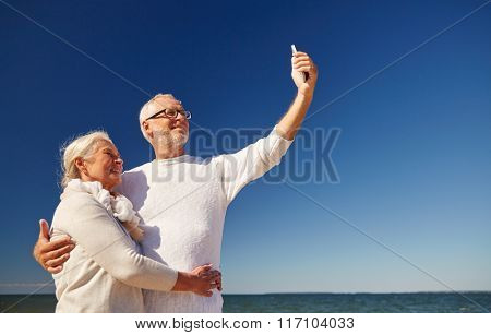 seniors with smartphone taking selfie on beach