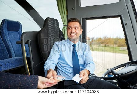bus driver with money selling ticket to passenger
