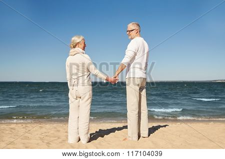 happy senior couple holding hands summer beach