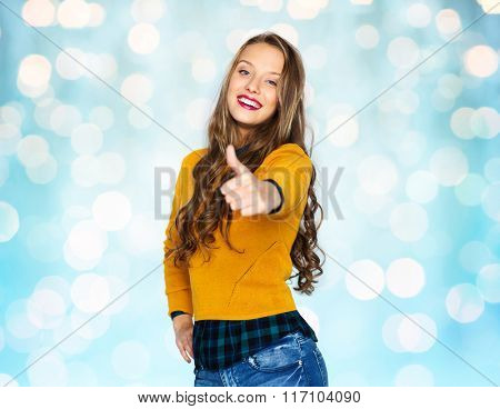 happy young woman or teen girl showing thumbs up