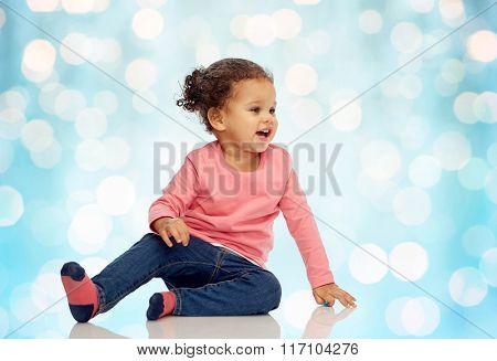smiling little baby girl sitting on floor