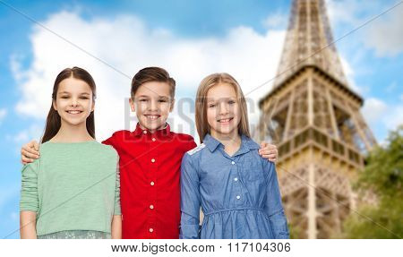 happy boy and girls hugging over eiffel tower