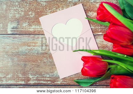 close up of tulips and greeting card with heart