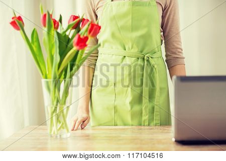 close up of woman with tulips in vase and laptop
