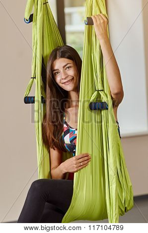portrait of sitting woman in anti-gravity aerial yoga