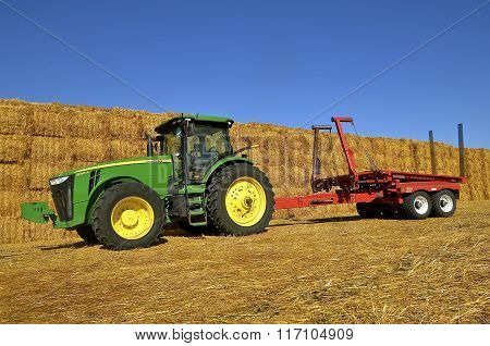 New John Deere tractor and trailer by a straw stack