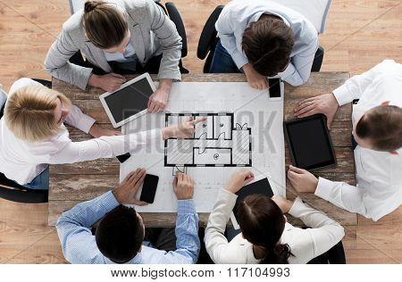 business team with blueprint and gadgets