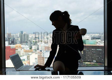Silhouette of businesswoman work near window in hotel room.
