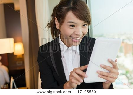 Asian business woman using tablet and thinking, closeup portrait in hotel room.