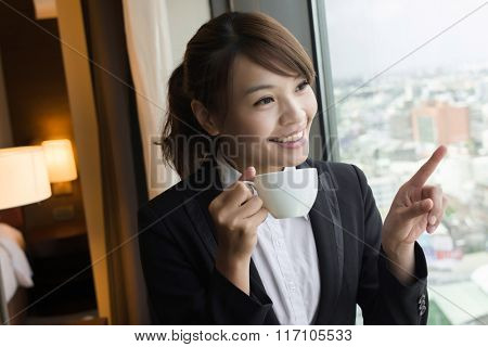Asian business woman holding a cup of coffee and looking into distance near the window in hotel room.