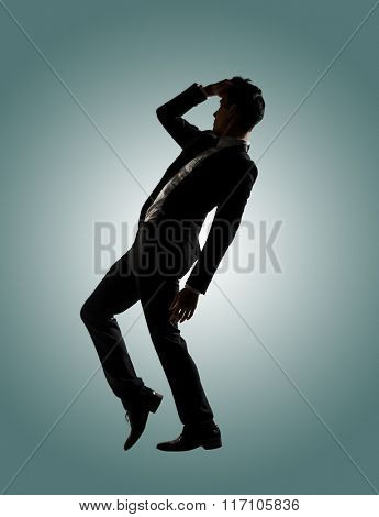 Silhouette of Asian businessman dancing or posing, isolated