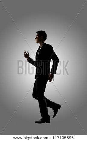 Confident businessman running, silhouette portrait isolated