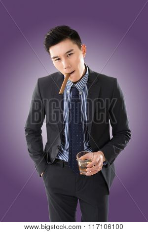 confident young Asian businessman holding a cigar