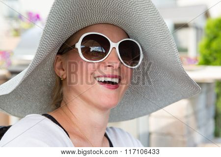 Woman In Hat And Sunglasses Laughing Outdoors