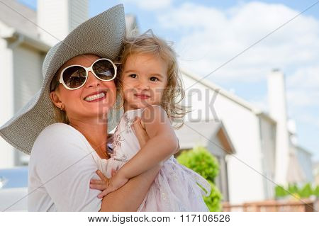 Mother And Daughter Hugging Outdoors In Summer