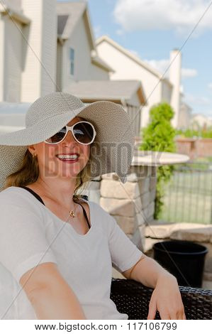 Woman In Hat And Sunglasses Sitting On Patio