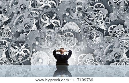 Businessman looking at gear mechanism