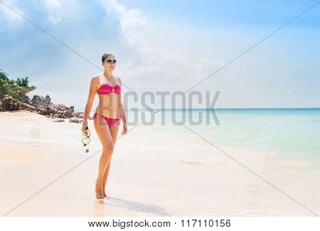 Beautiful, young lady in pink swimwear posing on the beach with diving mask.