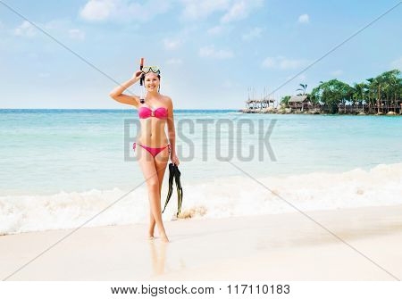 Gorgeous, slim, cheerful girl posing with diving mask and flippers on the seacoast in Thailand.
