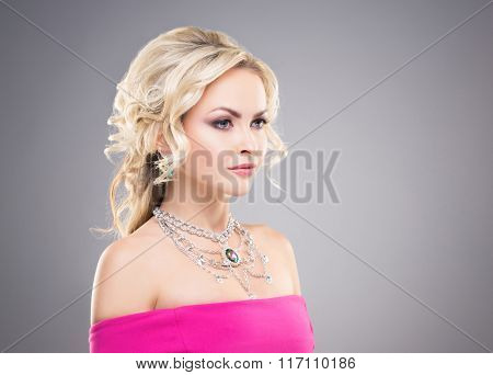 Side view of beautiful blond in pink dress wearing necklace with a gem over grey background.