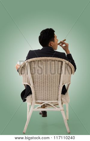 Cunning businessman of Asian sit on chair.