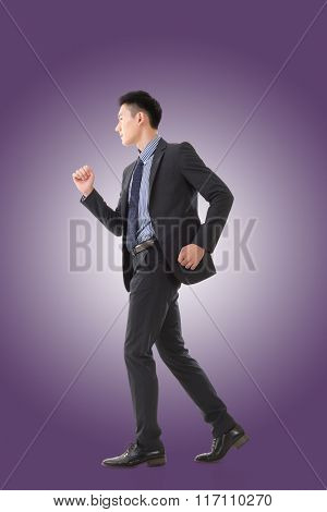 Attractive young business man running, full length portrait isolated.