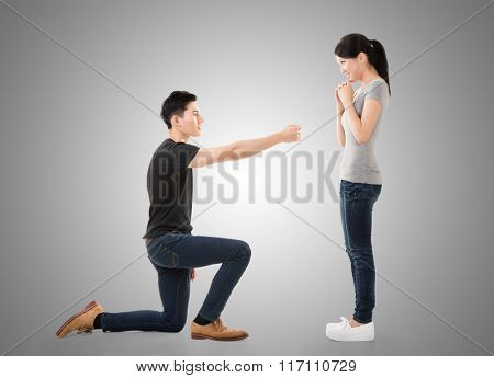 young Asian man propose to his girlfriend, studio shot