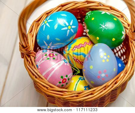 Wicker basket with easter eggs on wooden board
