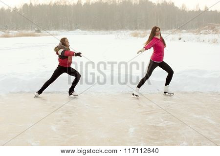 Coach of figure skating with apprentice practise at the frozen lake