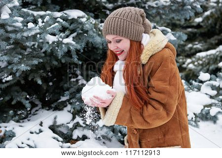 Woman take a handful snow in winter forest at day. Fir trees with snow.