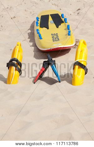 Lifesaving Raft, Floatation Devices And Swimming Fins On Beach