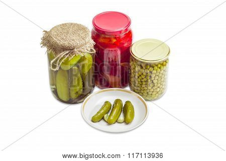Pickled Cucumbers On Saucer And Pickled Vegetables In Glass Jars