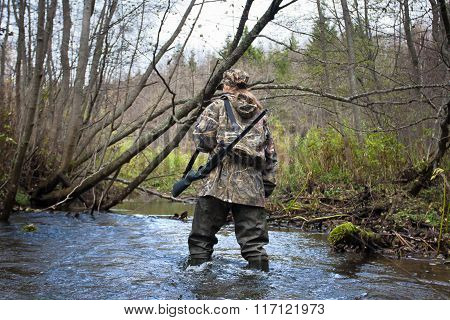 Woman Hunter In Waders Crossing Small River In The Forest