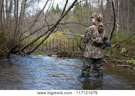 Woman Hunter In Waders Crossing The Forest River