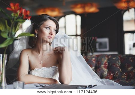 Elegant Bride In A White Dress Sits At Table