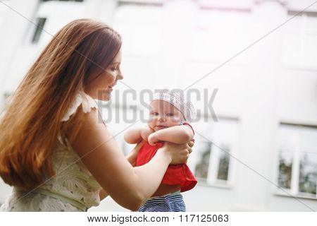 Loving Young Mother Holding And Kissing Her Baby