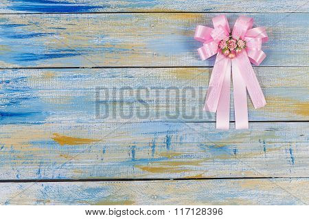 Pink Fabric Bow On Colored Wooden Background