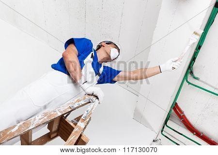 Painter Painting Ceiling With Brush