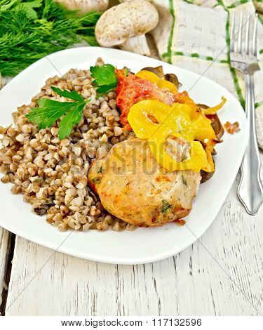 Cutlets of turkey with buckwheat and vegetables in plate on boar