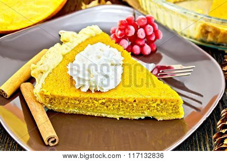 Pie pumpkin in plate with cream on dark board