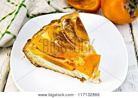 Pie with curd and persimmons in plate on light board