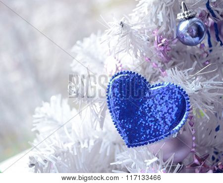 Blue Heart Hanging On Artificial Christmas Tree Branch. Christmas Decor. Winter Holidays