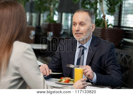 Successful business partners have a lunch in cafe