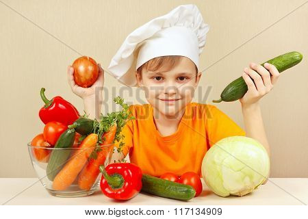 Little boy with vegetables at table
