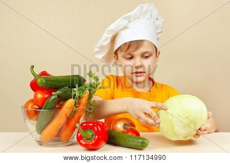 Little kid in chefs hat with vegetables at table