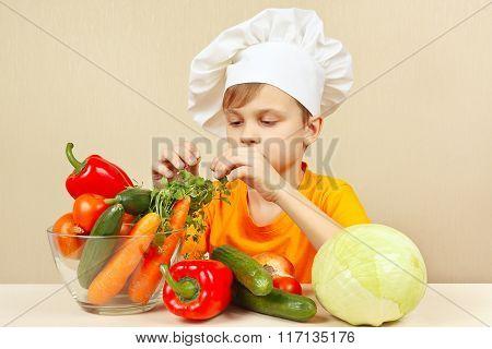 Little boy chooses fresh vegetables for salad at table