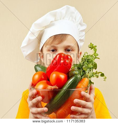 Little funny boy with fresh vegetables