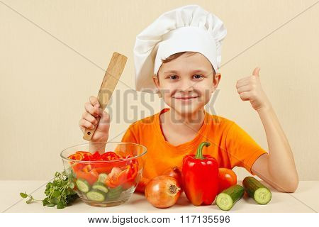 Little funny chef shows how to cook vegetable salad