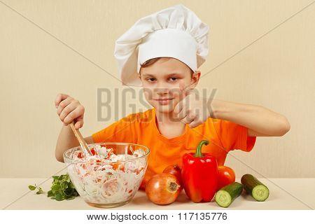 Little funny chef prepared salad of fresh vegetables