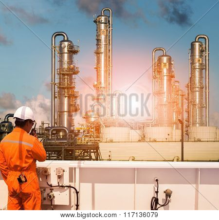 Working Man Wearing Safety Suit Talking Radio In Heavy Petrochemical Industry Plant